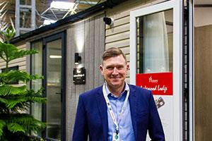 Gary Corlyon, managing director of Victory Leisure Homes, and the new Lakewood Lodge holiday home.