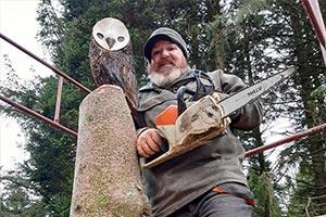 man with carved sculpture in cumbria park Skelwith
